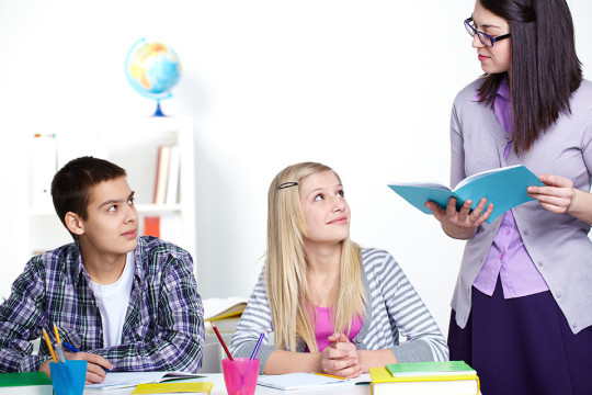 Portrait of teenage lad and girl looking at teacher while listening to her